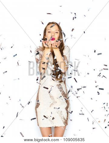 people, holidays, gesture and glamour concept - happy young woman or teen girl in fancy dress with sequins and confetti at party sending blow kiss
