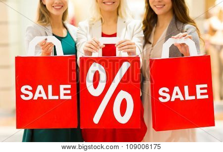 consumerism and people concept - close up of happy young women holding shopping bags with sale and percentage sign in mall