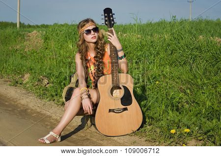 Young Hippie Girl Sitting On A Summer Field With Her Guitar