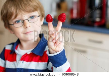 Kid boy eating fresh raspberries in kindergarten