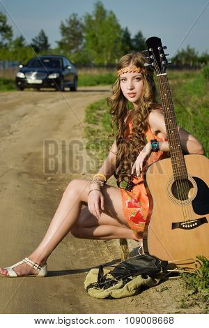 Hippie Girl Travelling With Her Guitar On A Road