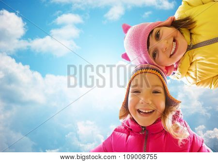 childhood, leisure, friendship and people concept - happy girls faces outdoors over blue sky and clouds background