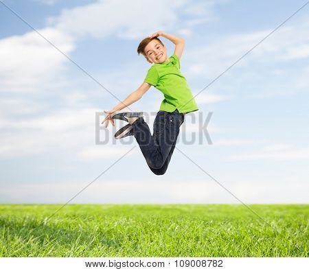 happiness, childhood, freedom, movement and people concept - smiling boy jumping in air over blue sky and grass background