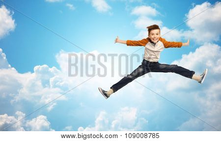 happiness, childhood, freedom, movement and people concept - happy smiling boy jumping in air over blue sky and clouds background