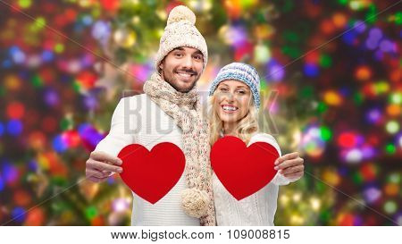 love, valentines day, couple, christmas and people concept - smiling man and woman in winter hats and scarf holding red paper heart shapes over lights background