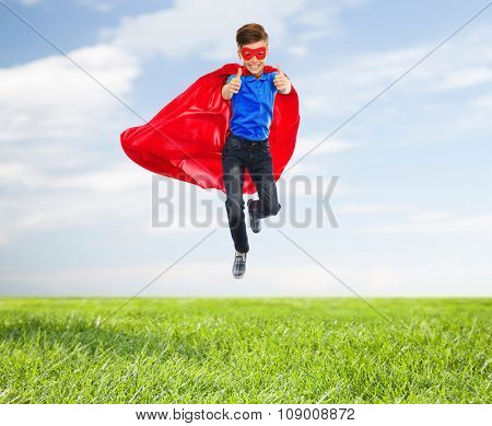 imagination, gesture, childhood, movement and people concept - boy in red super hero cape and mask flying in air and showing thumbs up over blue sky and grass background