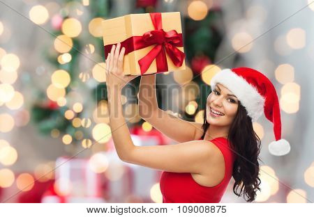 people, holidays, christmas and celebration concept - beautiful sexy woman in red dress and santa hat with gift box over holidays lights background