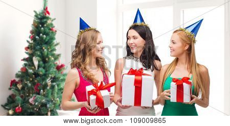 presents, holidays, people and celebration concept - smiling women in party caps with gift boxes over living room and christmas tree background