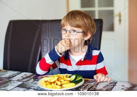 Kid boy eating fresh vegetables in kindergarten
