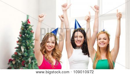 holidays, christmas, people, gesture and celebration concept - smiling women in party caps showing thumbs up over living room and christmas tree background