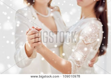 people, homosexuality, same-sex marriage and love concept - close up of happy married lesbian couple dancing over snow effect