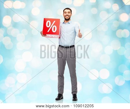 people, sale, shopping, discount and christmas concept - smiling man holding red percentage sign over blue holidays lights background