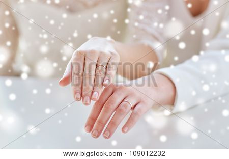 people, homosexuality, same-sex marriage and love concept - close up of happy lesbian couple hands showing wedding rings on over snow effect