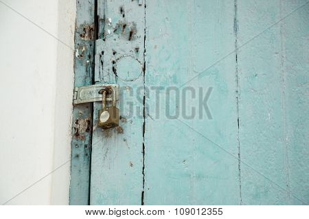 Old padlock on a wooden door. old dirty wooden door with rusty locks and bolts