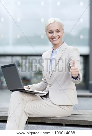 business, education, technology and people concept - smiling businesswoman working with laptop computer on city street