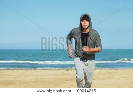 Young Man Jogging On A Beach