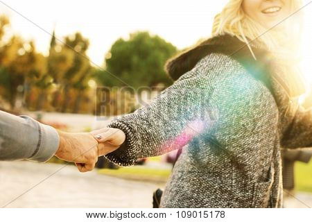 young happy woman pulling hand of a guy say follow me