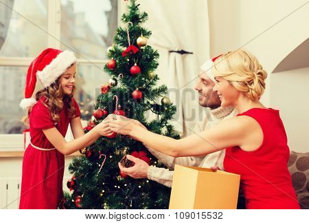 family, christmas, x-mas, happiness and people concept - smiling family in santa helper hats decorating christmas tree