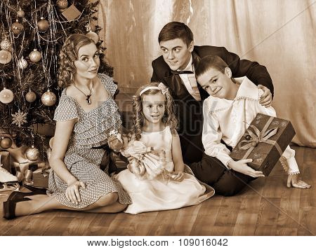 Happy family with children  and handsome father receiving gifts under Christmas tree. Black and white retro