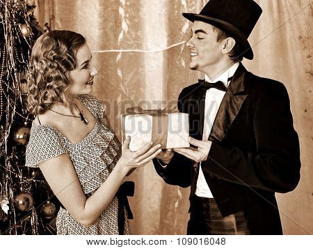 Couple traditionally dressed on party near Christmas tree. Black and white retro vintage.