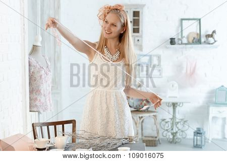 Young blonde woman making home decoration.