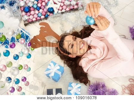 Happy woman lying on floor, enjoying christmas decoration, smiling.