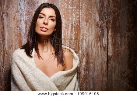 Portrait of beautiful sexy woman in blanket, looking at camera, front of wooden surface.