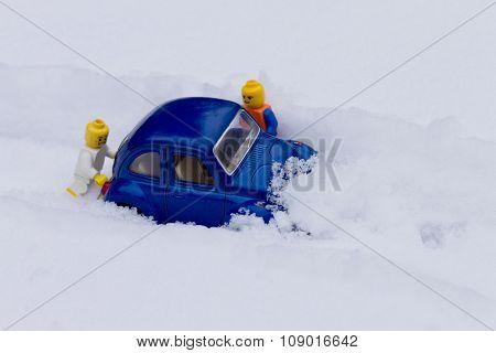 Man pushing car stuck in the snow.