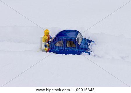 Men pushing car stuck in snow. Toy models.