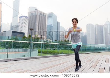 Asian Young Woman checking the data on sport watch while jogging