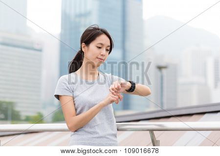 Asian Young Woman use of the wearable watch before jogging