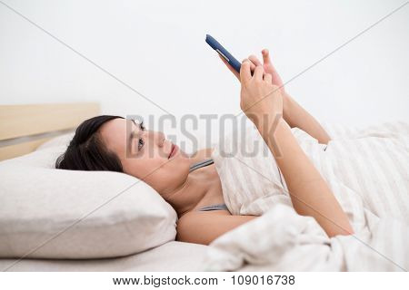 Woman using the mobile phone and lay down in bed