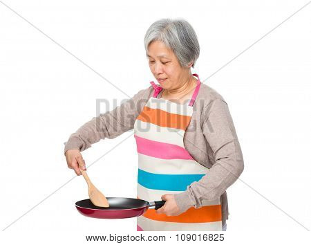 Asian Old woman  cooking with frying pan