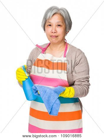 Old woman use of the bootle spray and rag