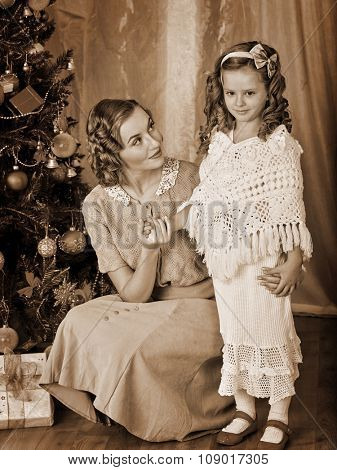 Daughter and loving mother receiving near Christmas tree. Black and white retro vintage.