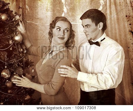 Young happy family on party near Christmas tree celebrate their first Xmas. Black and white retro vintage.