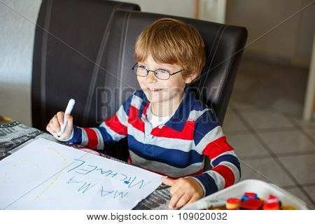 Kid boy in glasses making school homework at home