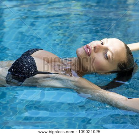 Beautiful fashion woman in pool. Sexy girl with full lips wearing stylish bikini poses swimming at r