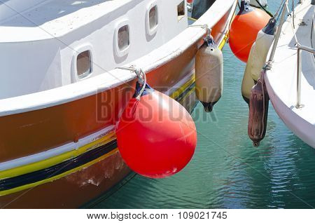 Two Boats With Orange And White Buoys