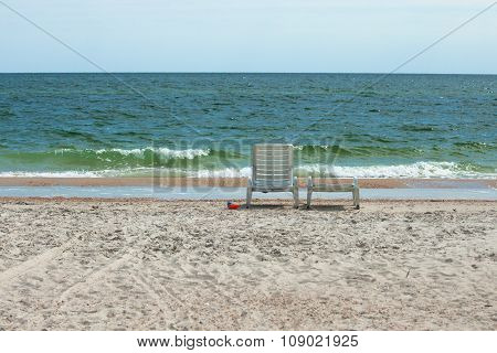 Two white plastic deck chairs on the sandy beach