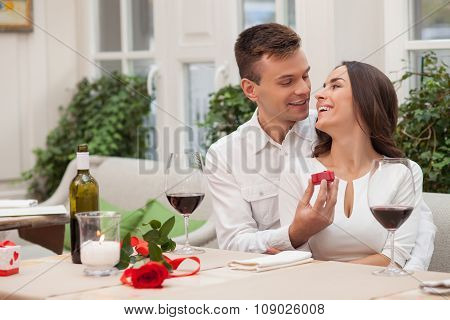 Cheerful boyfriend and girlfriend are dating in cafe