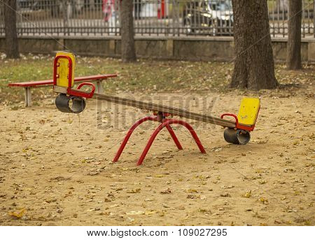 Kids seesaw on sandy playground in city park