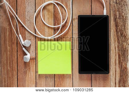 Closeup Of Black Smartphone With Headphones And Sticky Notes On Wooden Surface