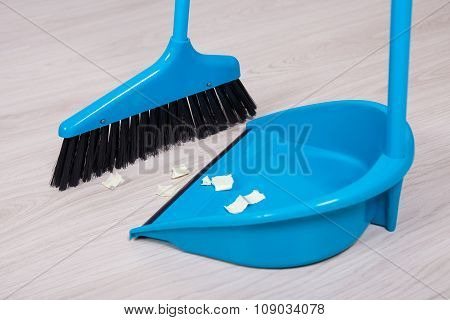 Close Up Of Broom And Dustpan With Paper Trash