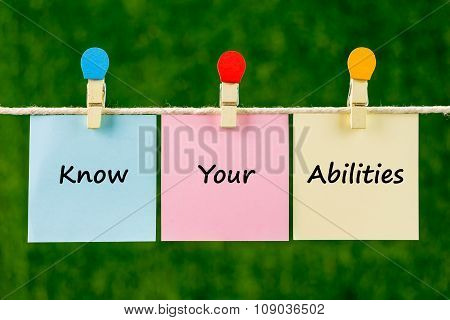 Words Of Know Your Abilities On Sticky Color Papers Hanging By A Rope.