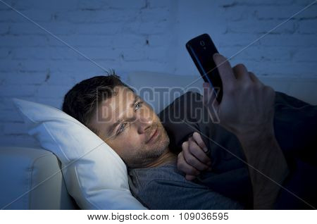 Young Man In Bed Couch At Home Late At Night Using Mobile Phone In Low Light Relaxed In Communicatio