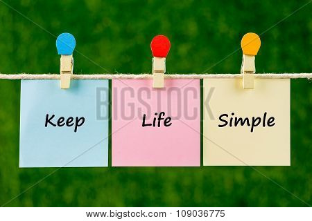 Words Of Keep Life Simple On Sticky Color Papers Hanging By A Rope.