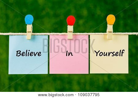 Words Of Believe In Yourself On Sticky Color Papers Hanging By A Rope.