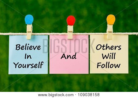 Word Quotes Of Believe In Yourself And Others Will Follow On Sticky Color Papers Hanging On Rope.