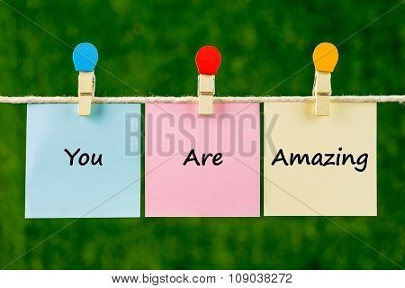 Word Quotes Of You Are Amazing On Sticky Color Papers Hanging On Rope.